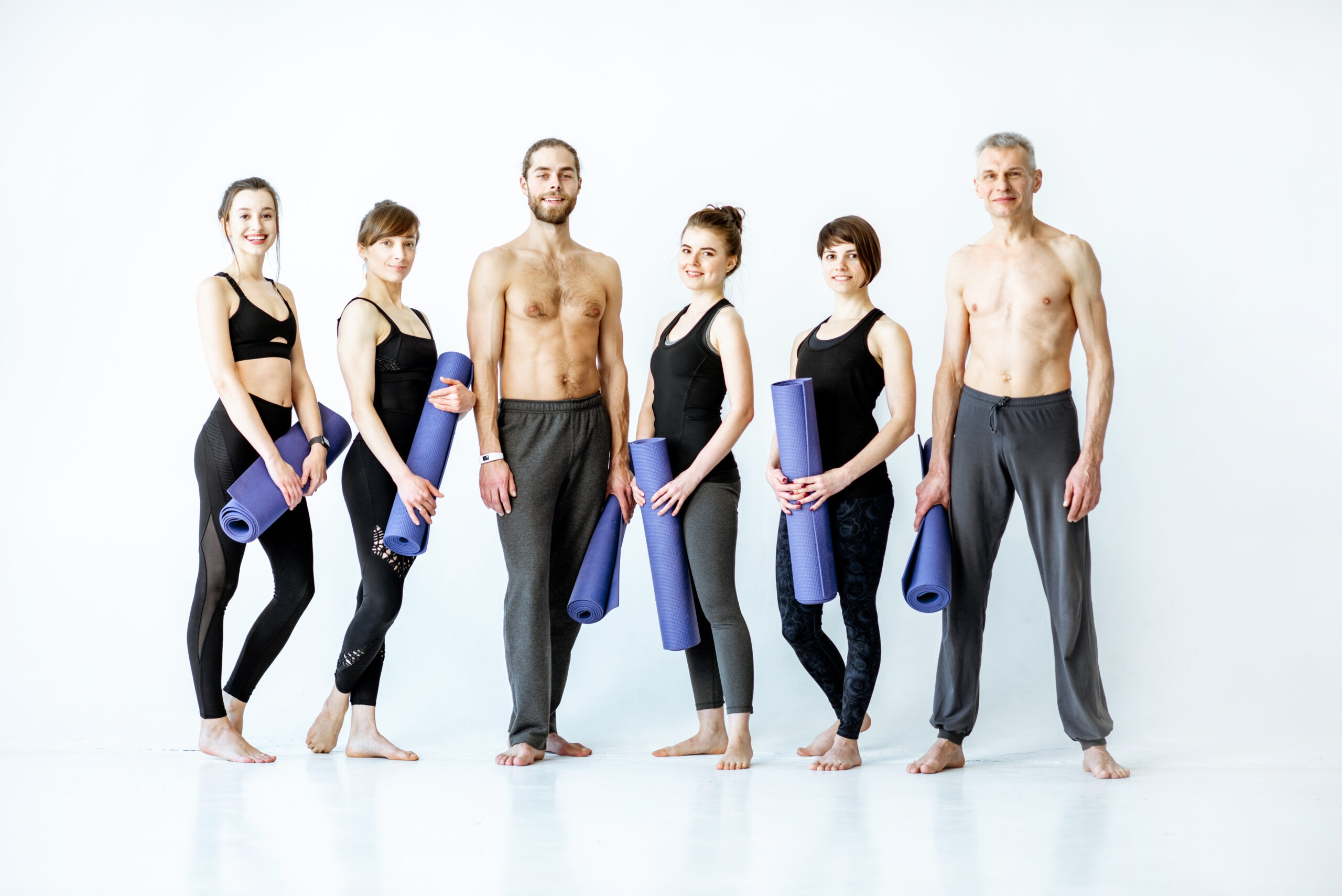 Group Of People In Sportswear With Fitness Mats In The Studio